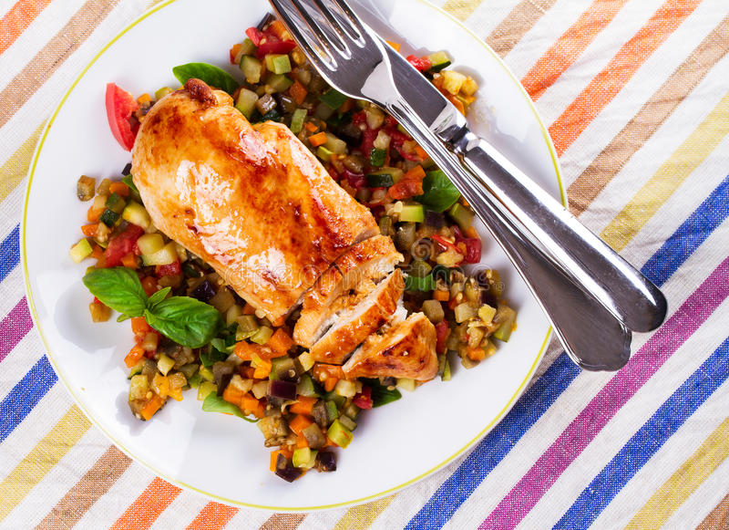 Fried chicken breast with sauteed vegetables. Eggplant, carrot, zucchini, squash and tomatoes. View from above, top studio shot stock photography