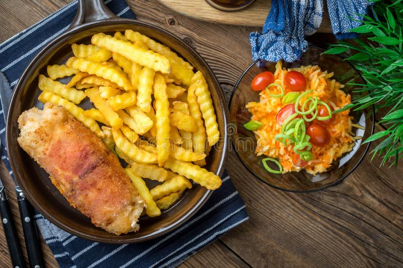 Fried chicken breast stuffed with mushrooms and cheese wrapped i. N ham served with fries and salad. Small depth of field royalty free stock photo