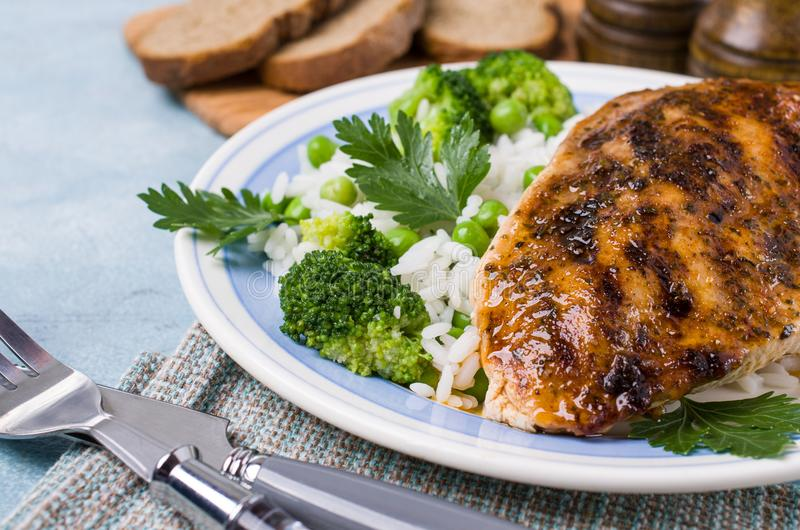 Fried chicken breast. With white rice and green vegetables. Selective focus stock photography