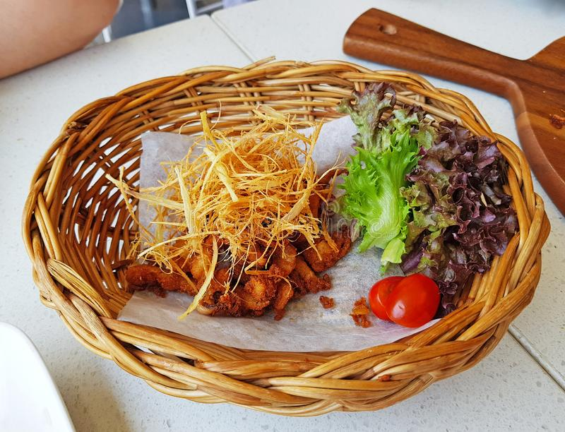 Fried chicken with crispy lemon grass in weave basket stock photography