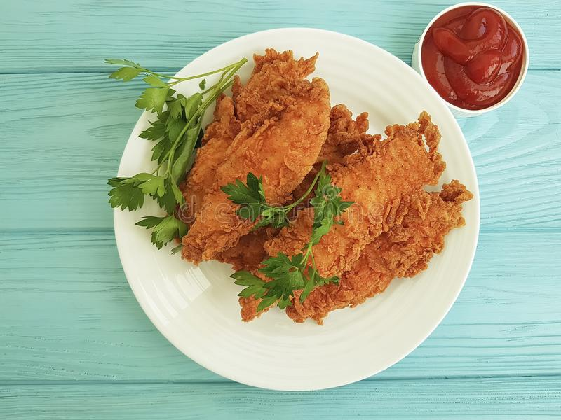 Fried chicken fried delicious lunch dinner in breading, parsley, ketchup on blue wooden. Fried chicken in breading parsley ketchup on blue wooden fried delicious stock photos