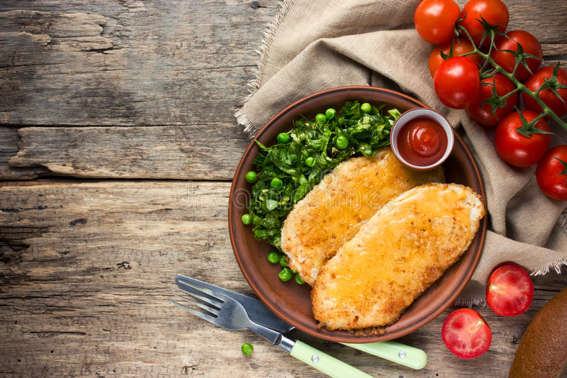 Fried chicken fillet with cheese crust and garnish of fresh vegetables, healthy food royalty free stock photos