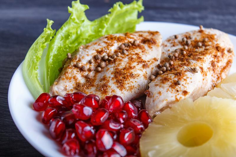 Fried chicken fillets with lettuce, pineapple and pomegranate seeds on black wooden background. Copy space, close up stock image