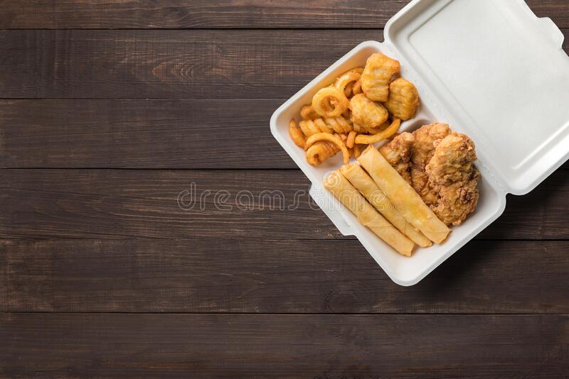 Fried chicken, french fries with cheeseburger spring rolls on wooden background. Copyspace for text and logo. Top view. Fried chicken, french fries with royalty free stock photos