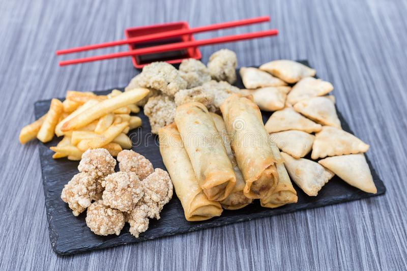 Fried chicken, gyozas, french fries, meat and mushrooms balls on a wooden table royalty free stock photos