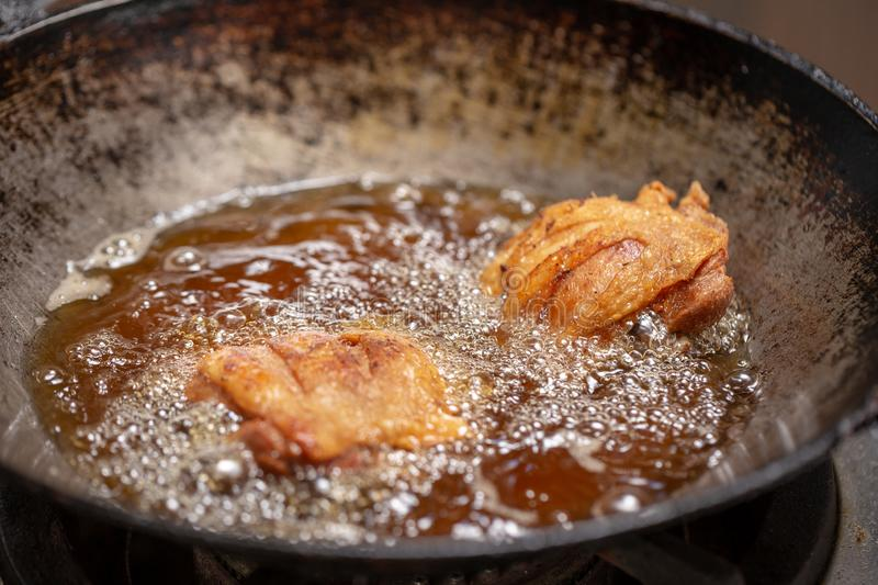 Fried chicken in hot oil and boiling in pan. Background, bird, black, cast-iron, cook, cooking, deep, delicious, diet, dinner, fatty, food, fry, frying royalty free stock photo