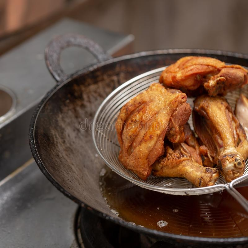 Fried chicken in hot oil and boiling in pan. Fried chicken in a basket for drain oil, background, bird, black, boil, boiling, cast-iron, cook, cooking, deep royalty free stock photography