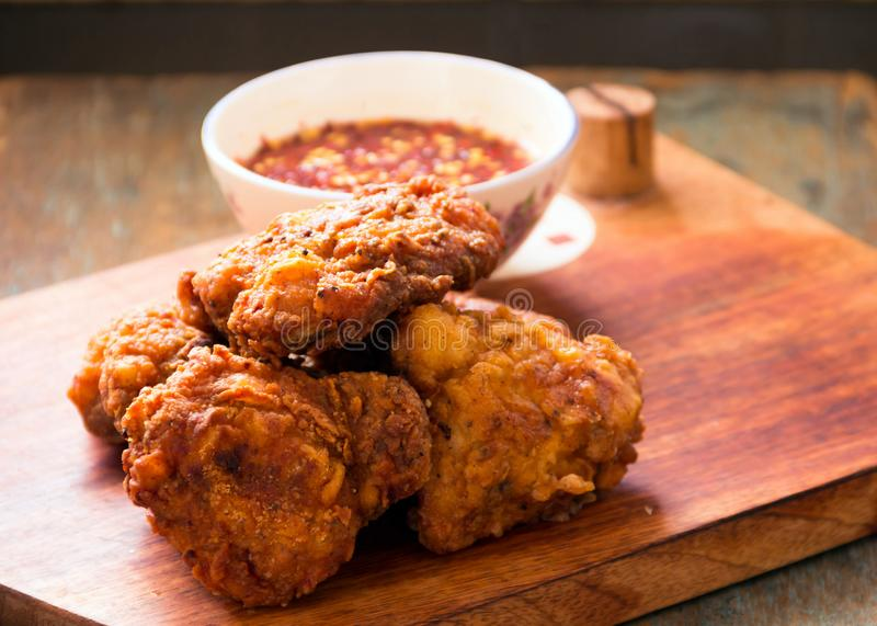 Fried Chicken with Hot Sauce on a Wooden Board royalty free stock photography