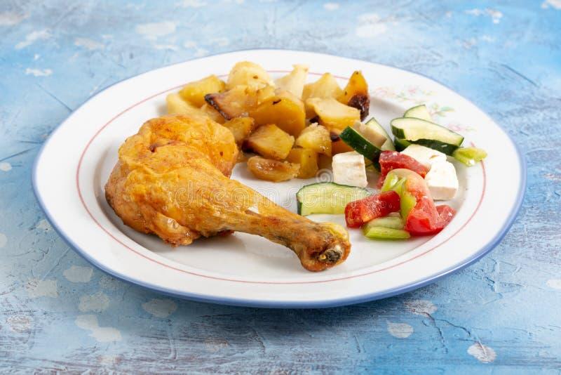 Fried Chicken Leg With Potatoes et salade de la Grèce du plat images libres de droits