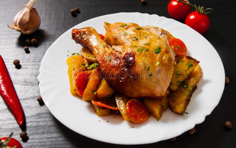Fried chicken legs with carrots, onions and potatoes served on a white plate stock image