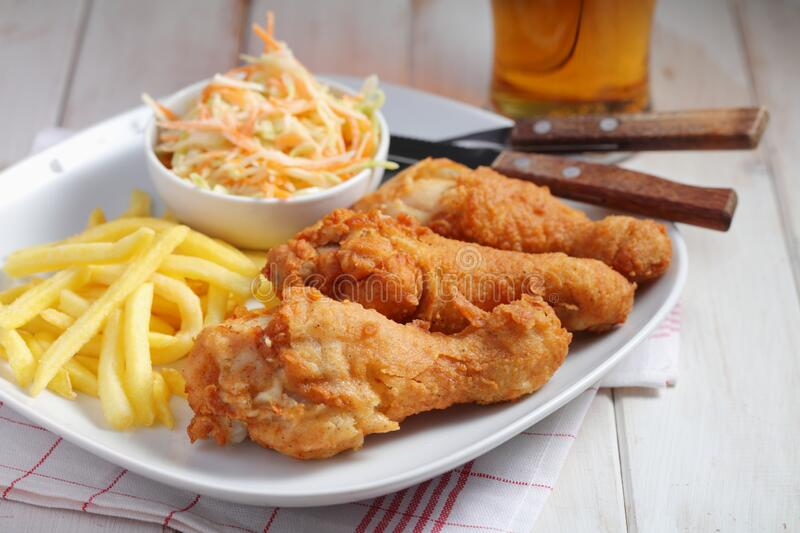 Fried chicken legs with French fries, cole slaw, and beer royalty free stock images