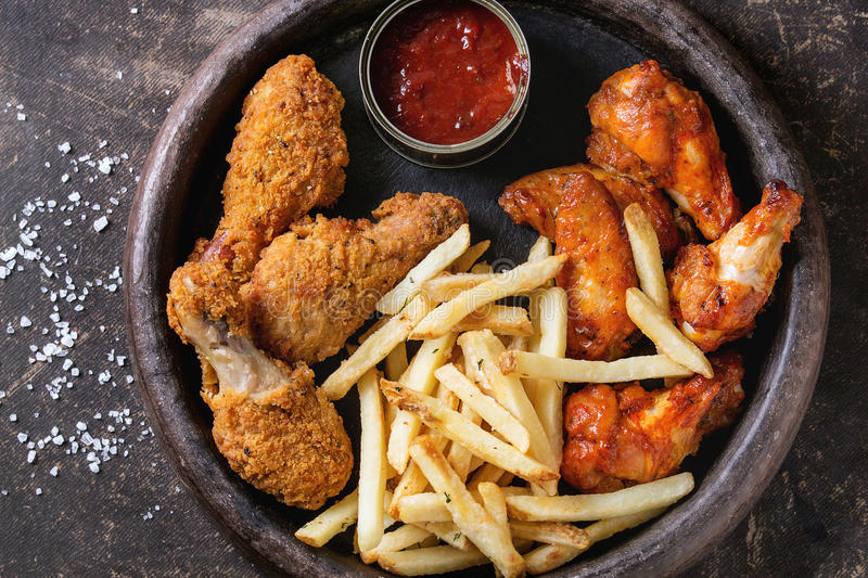 Fried chicken legs with french fries. Fast food fried crispy and spicy chicken legs, wings and french fries potatoes with salt and ketchup sauce served in stone stock photos