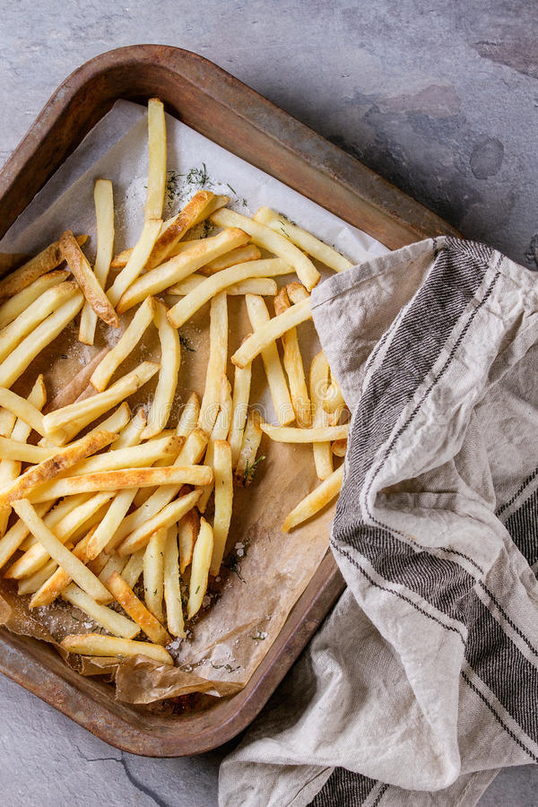 Fried chicken legs with french fries. Fast food french fries potatoes with skin served with salt on baking paper in old rusty oven tray with kitchen towel over royalty free stock photo
