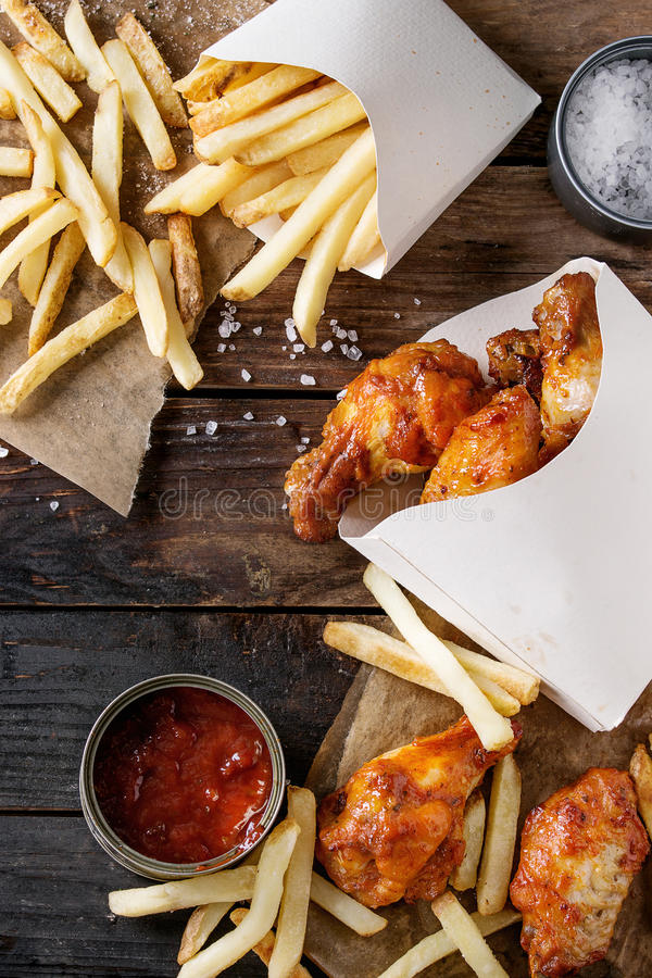Fried chicken legs with french fries. Fast food fried spicy chicken legs, wings and french fries potatoes in lunch boxes with salt and ketchup sauce served on royalty free stock images