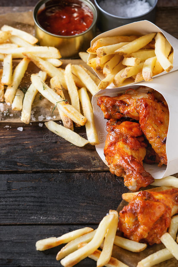 Fried chicken legs with french fries. Fast food fried spicy chicken legs, wings and french fries potatoes in lunch boxes with salt and ketchup sauce served on stock photography