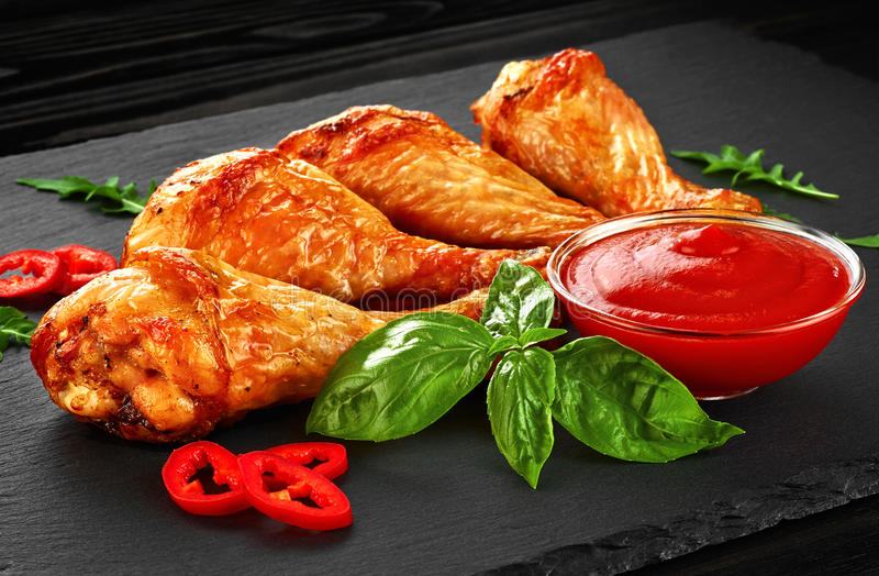 Fried chicken legs with ketchup, chili pepper and basil stock images