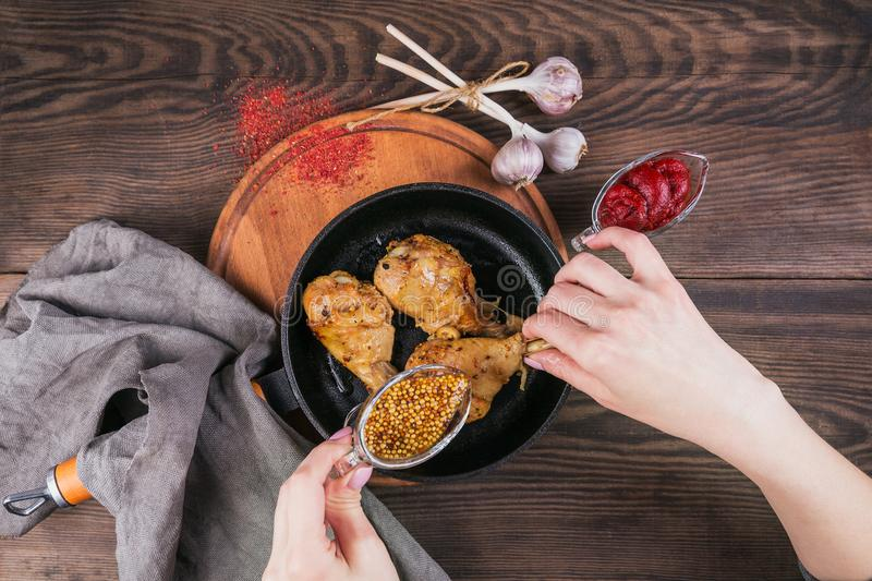 Fried chicken legs with sauces in pan stock photos