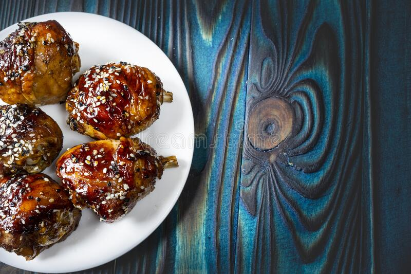 Fried chicken legs with teriyaki sauce and sesame seeds on a white plate. royalty free stock photography