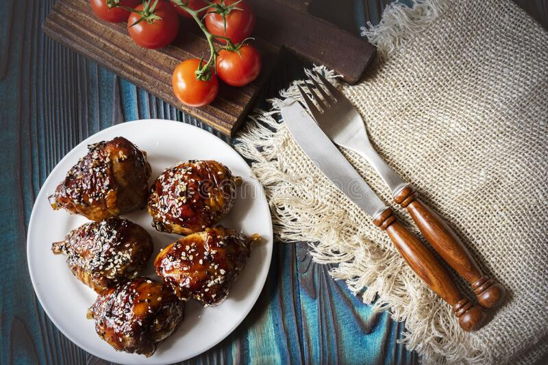 Fried chicken legs with teriyaki sauce and sesame seeds on a white plate. royalty free stock images