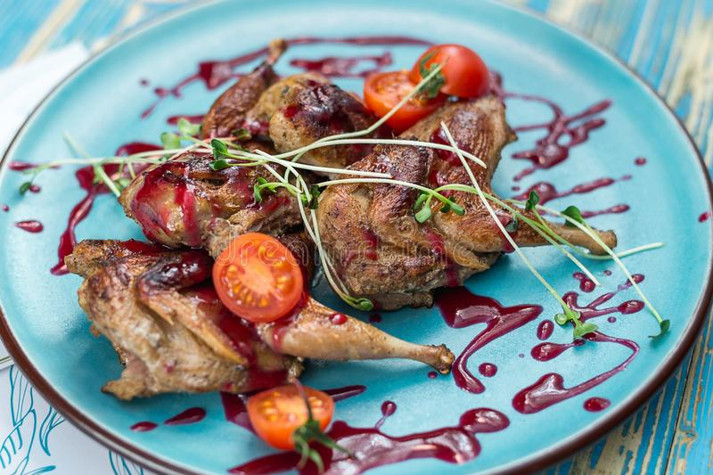 Fried chicken legs with tomatoes on a blue plate. Horizontal frame royalty free stock image