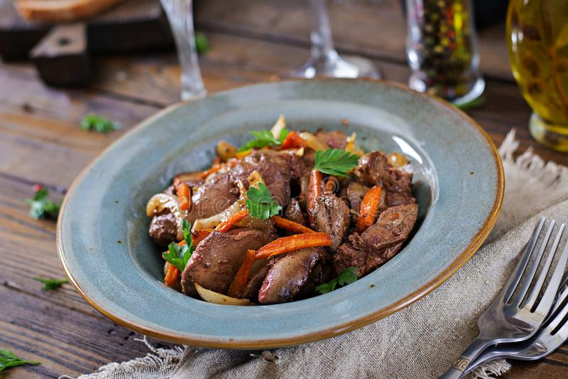 Fried chicken liver with vegetables. Healthy food. Wood background royalty free stock images