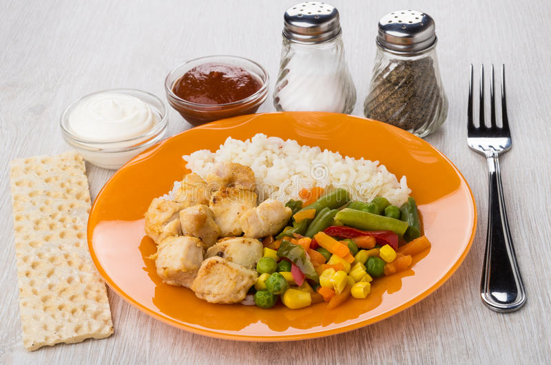 Fried chicken meat with rice, vegetables, salt, pepper, sauces, royalty free stock image