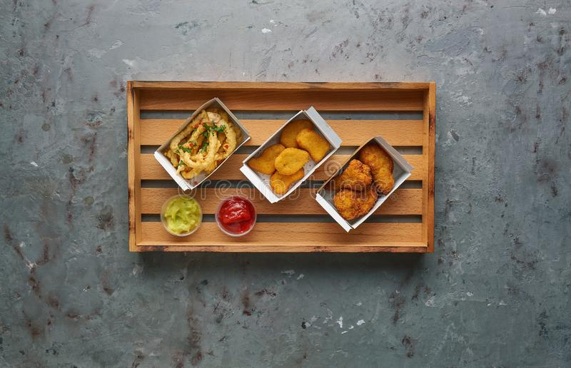 Fried chicken nuggets with legs and crispy octopus on wooden tray, top view, copy space. Street food concept, horizontal royalty free stock images