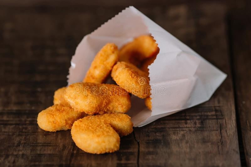 Fried chicken nuggets in a paper bag on wood royalty free stock images