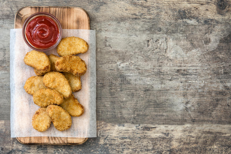 Fried chicken nuggets on wood stock images
