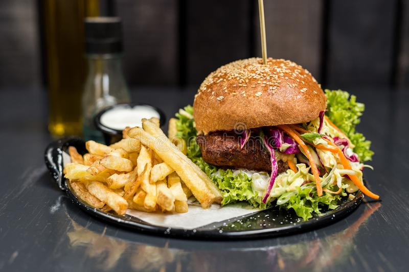 Fried chicken sandwich with vegetables and french fries on a wooden table royalty free stock images