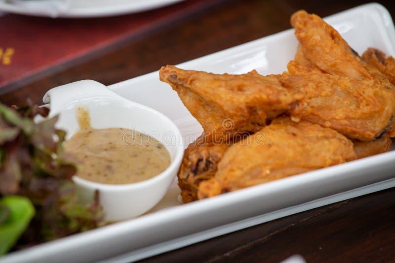Fried Chicken, sauce et l?gumes organiques, admirablement d?cor?s dans le plat blanc photo stock