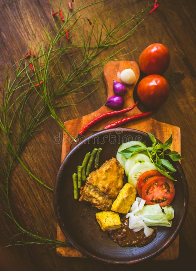 Fried chicken served with shrimp paste sauce. Shrimppaste, tofu, tempeh, onion, cucumber, beans, tomato, garlic, wooden, table, background, chilli, restaurant royalty free stock images