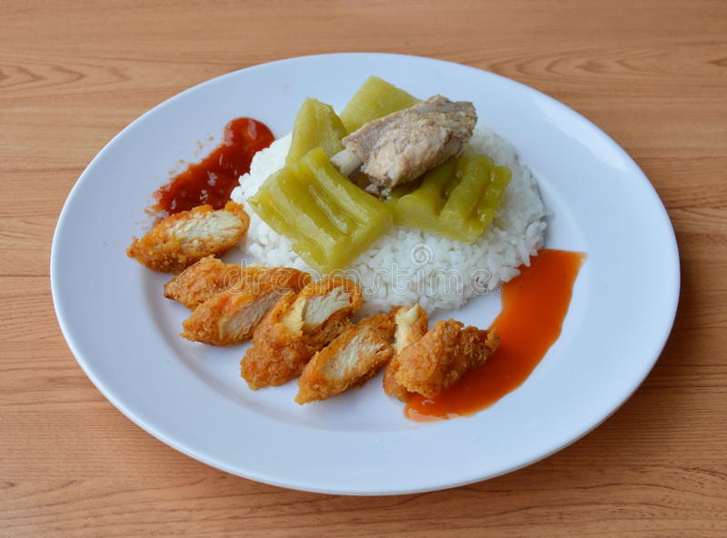 Fried chicken slice and boiled bitter cucumber with pork bone on rice royalty free stock image