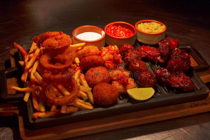 Fried Chicken Strips, fega vingar, lökcirklar, fiskpinnar och pommes frites som delar, Pune royaltyfria bilder