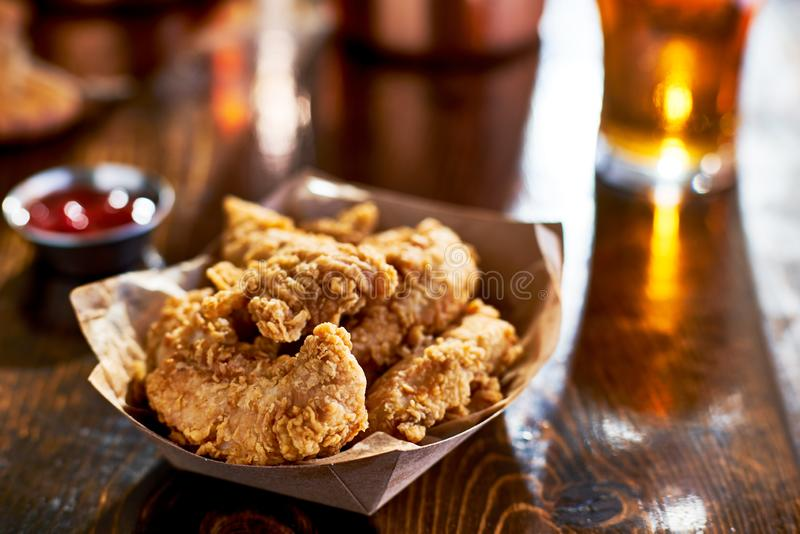 Fried chicken tenders in paper basket. Shot with selective focus royalty free stock photo
