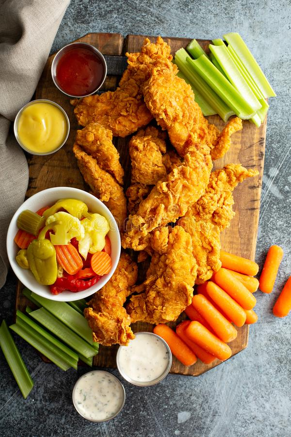 Fried chicken tenders with veggies. And sauces stock images