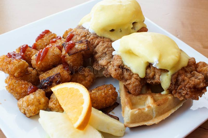 Fried chicken and waffles with eggs benedict on top. Fried chicken and waffles with eggs Benedict and Hollandaise sauce. Hearty breakfast at a restaurant royalty free stock photos
