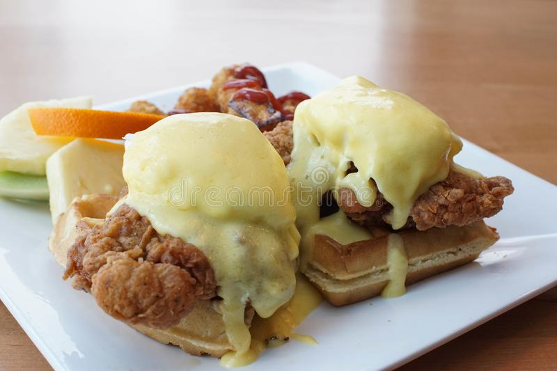 Fried chicken and waffles with eggs benedict on top. Fried chicken and waffles with eggs Benedict and Hollandaise sauce. hearty breakfast at a restaurant royalty free stock photo