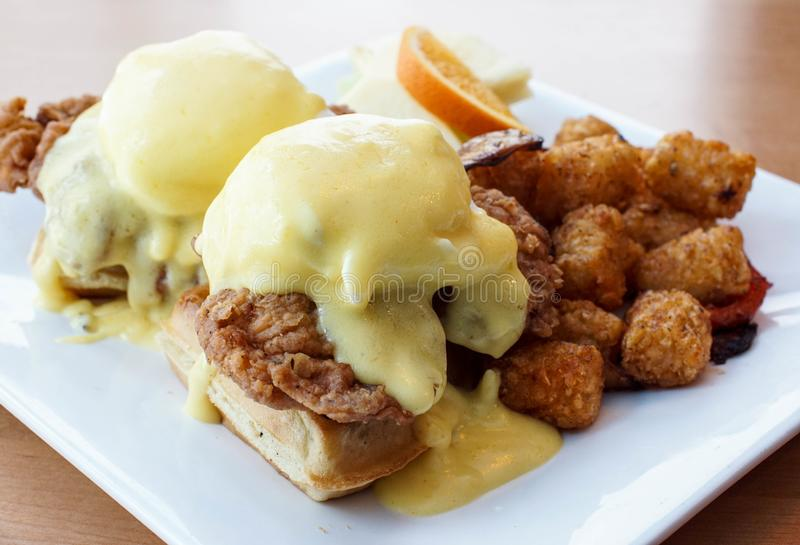Fried chicken and waffles with eggs benedict on top. Fried chicken and waffles with eggs Benedict and Hollandaise sauce. Hearty brunch at a restaurant. Southern stock photos