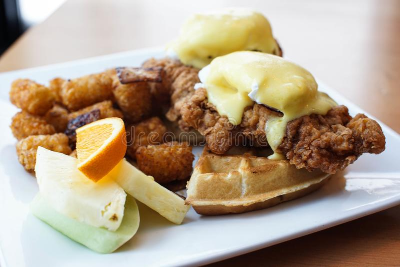 Fried chicken and waffles with eggs benedict on top. Fried chicken and waffles with eggs Benedict and Hollandaise sauce. Hearty brunch at a restaurant. Southern stock image