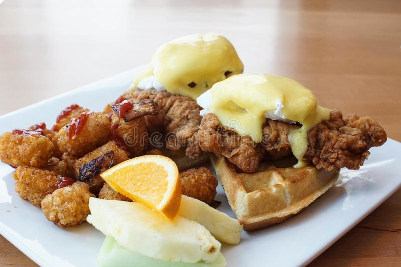 Fried chicken and waffles with eggs benedict on top. Fried chicken and waffles with eggs Benedict and Hollandaise sauce. Hearty brunch at a restaurant. Southern stock photo