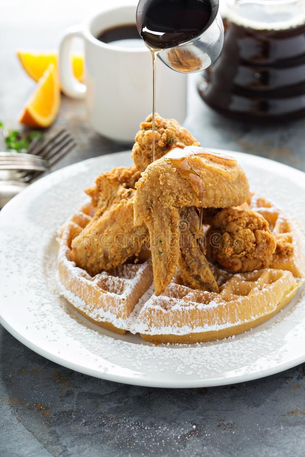 Fried chicken and waffles. With syrup pouring, southern food concept stock photo