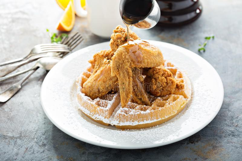 Fried chicken and waffles. With syrup pouring, southern food concept stock photos