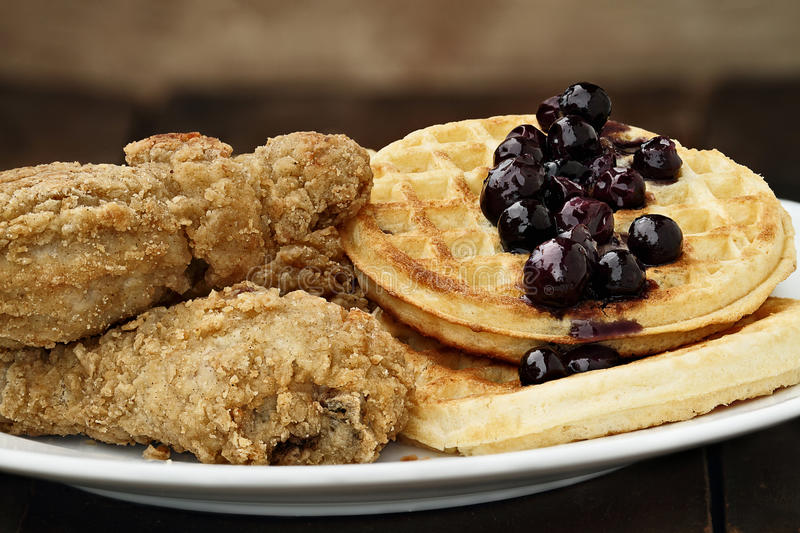 Fried Chicken and Waffles. Three pieces of deep fried chicken with waffles served with fresh blueberry sauce. Extreme shallow depth of field royalty free stock image