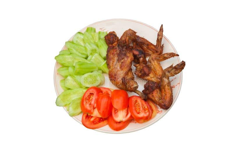 Fried Chicken Wing med fisksås med den nya tomaten och gurkan på plattan som isoleras royaltyfri foto