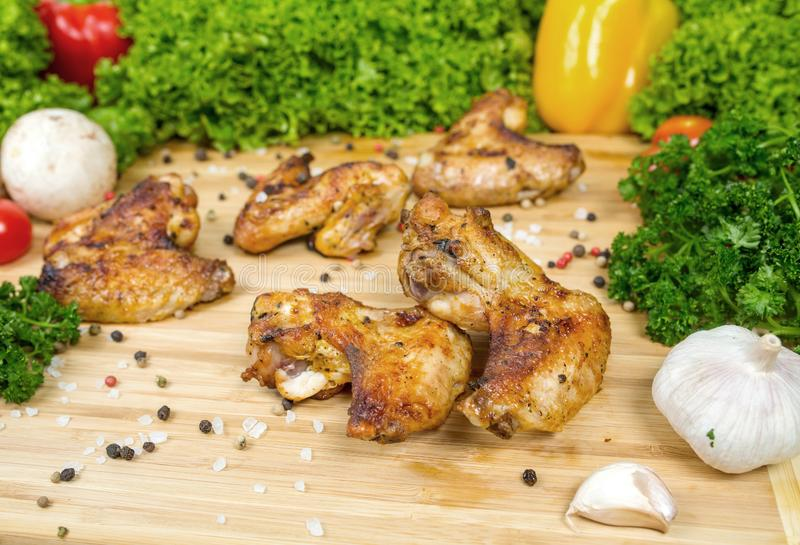 Fried chicken wings, baked chicken on a wooden board with cherry tomatoes, lettuce leaves, garlic, chilli pepper stock images