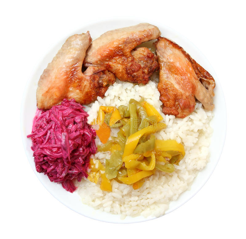 Fried chicken wings, boiled rice, pepper, beet on a white plate stock images