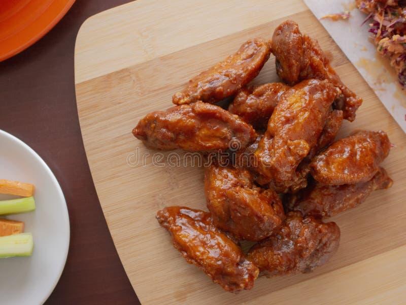 Fried Chicken Wings Covered en salsa caliente verdadera del Bbq con un lado de Cole Slaw Carrots y del apio desempe?? servicios e fotografía de archivo