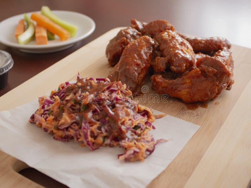 Fried Chicken Wings Covered en véritable sauce chaude à BBQ avec un côté de Cole Slaw Carrots et de céleri a servi sur une planch images stock