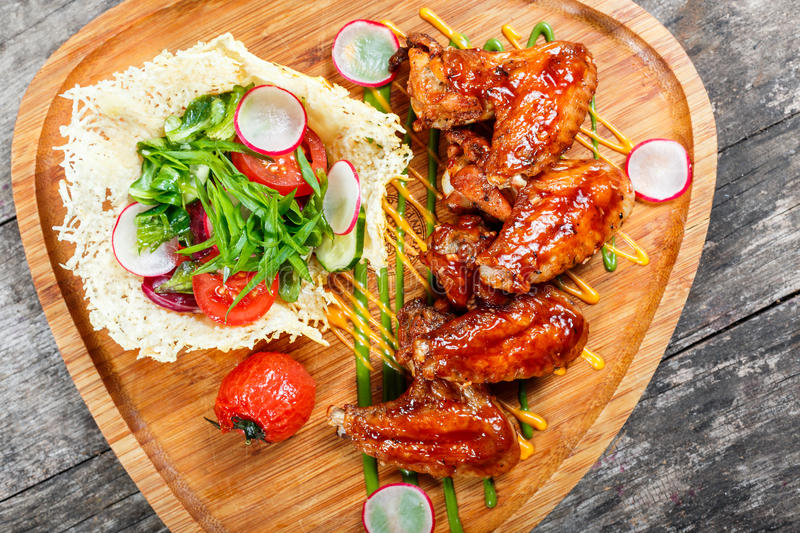 Fried chicken wings with fresh salad, grilled vegetables and bbq sauce on cutting board on wooden background stock images